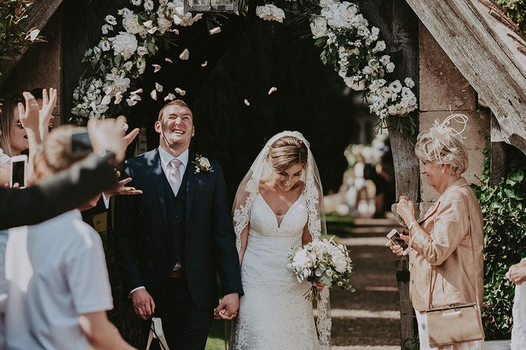 Bride and Groom Church Confetti Moment with Floral Arch Backdrop