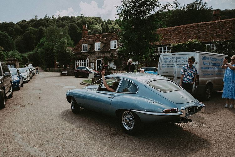 Bride and Groom Leaving the Church in a Blue E-Type Jaguar Wedding Car