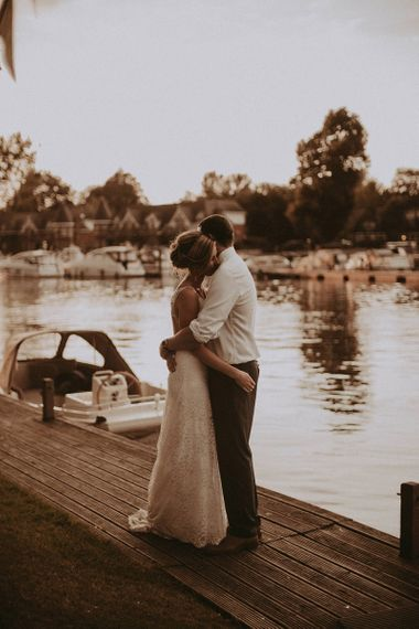 Bride and Groom Embracing by The River Bank
