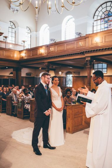 Black Bride and groom saying 'I do' at church ceremony