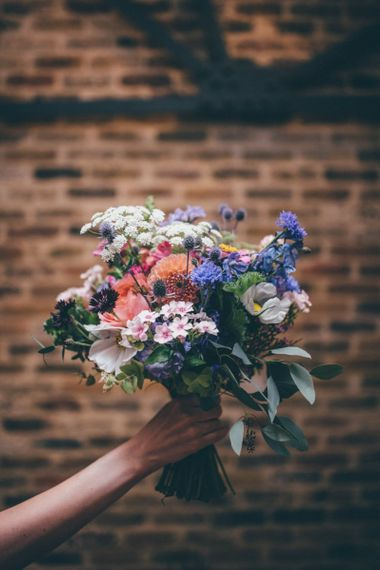 Beautiful wildflower wedding bouquets with pink and purple detail for city wedding with fairy light backdrop