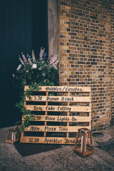 Wooden pallet order of the day sign at industrial wedding with fairy light backdrop