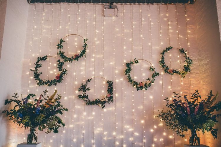 Industrial themed wedding decor with floral hoop foliage and fairy light backdrop