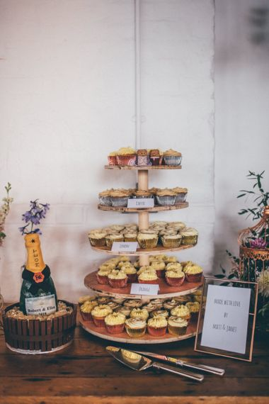 Wooden cake stand with cupcake wedding tower and champagne celebration cake