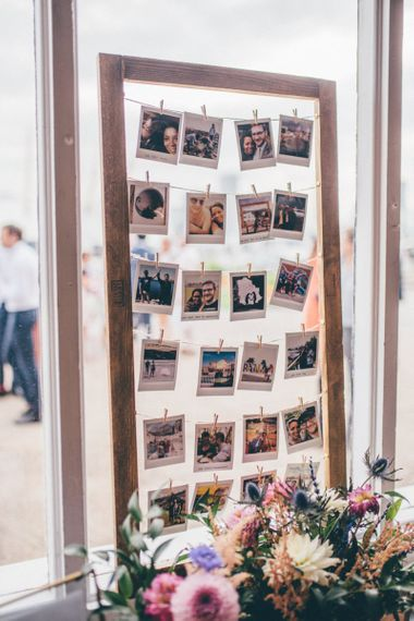 Polaroid guestbook at industrial styled city celebration with fairy light backdrop