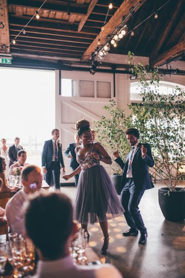 Wedding guests celebrate and industrial styled venue with fairy light backdrop in London