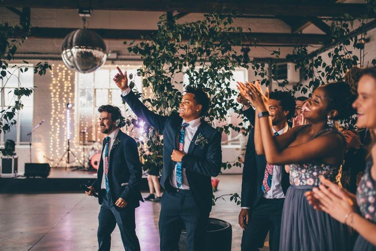 EWedding guests celebrate and industrial styled venue with fairy light backdrop in London