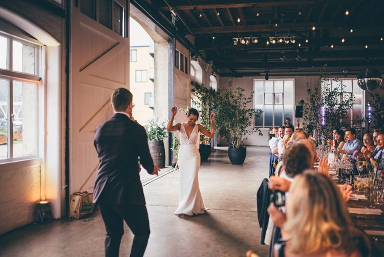 Bride and groom celebrate and industrial styled venue with fairy light backdrop in London
