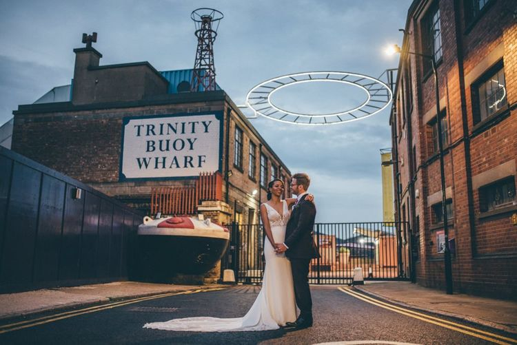 Bride and groom steal a moment at Trinity Buoy Wharf wedding reception with fairy light backdrop