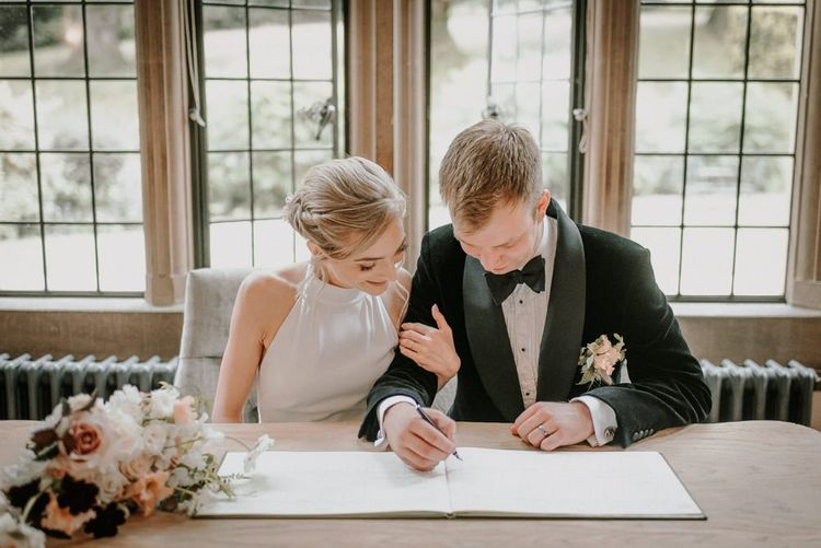 Bride And Groom Sign The Wedding Register At Coombe Lodge