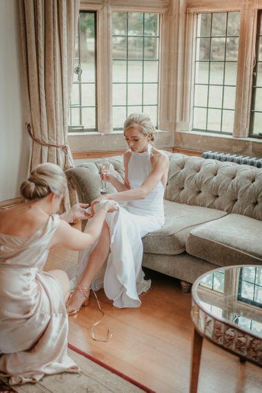 Bridal Préparations In Stella McCartney Wedding Dress With Bride Putting Wedding Shoes on