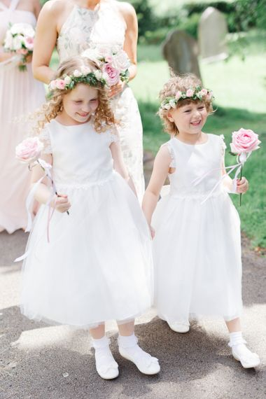 Flower girls in white dresses holding a pink flower stem and flower crown