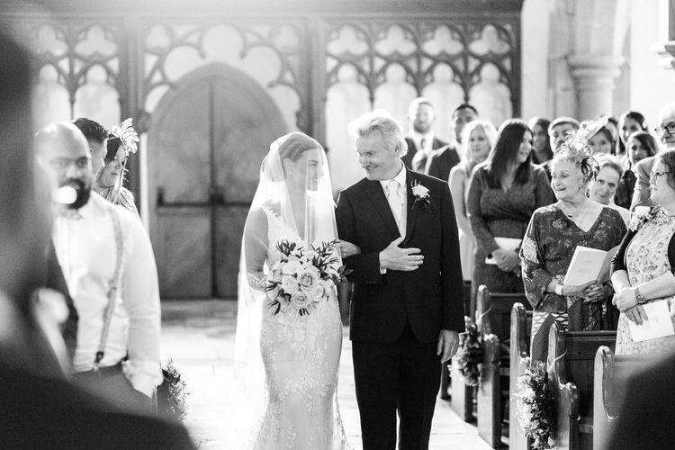 Father of the bride walking his daughter down the church aisle
