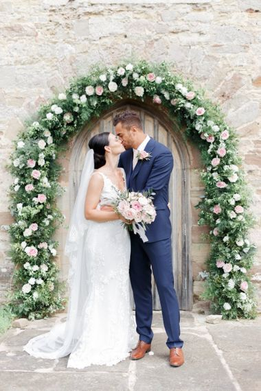Bride and groom portrait in front of a floral arch