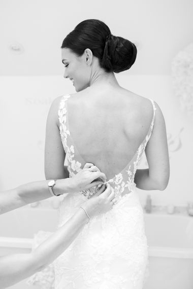 Bride with sleek bun a low back Pronovias wedding dress