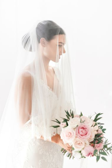 Bride holding a pink bouquet with a wedding veil