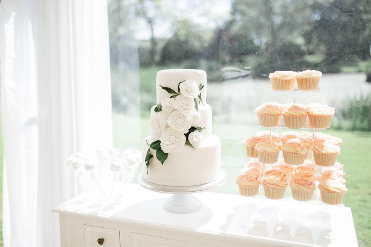 White wedding cake with rose wedding decor