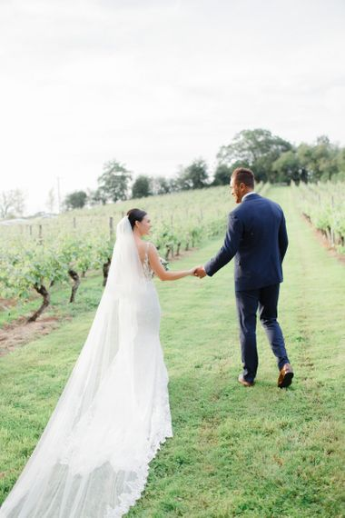 Bride and groom walking through the vineyard at Coddington