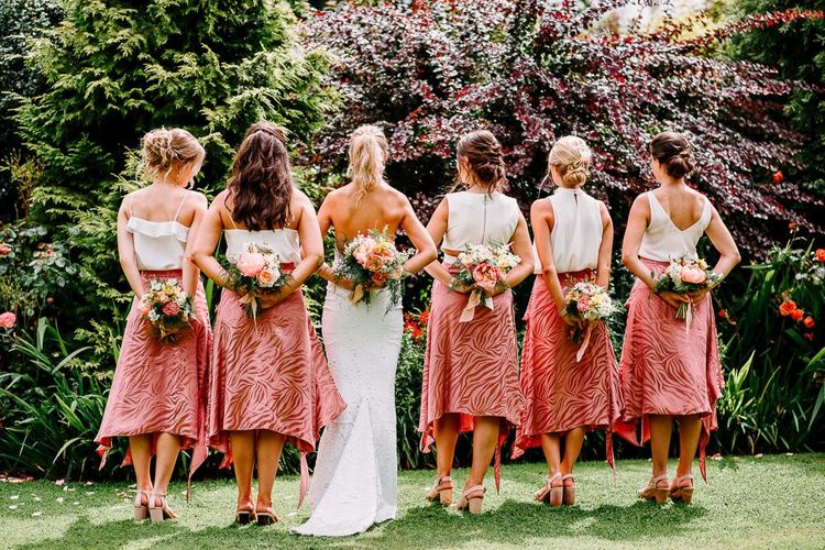 Backless wedding dress with bridesmaids in pink skirt