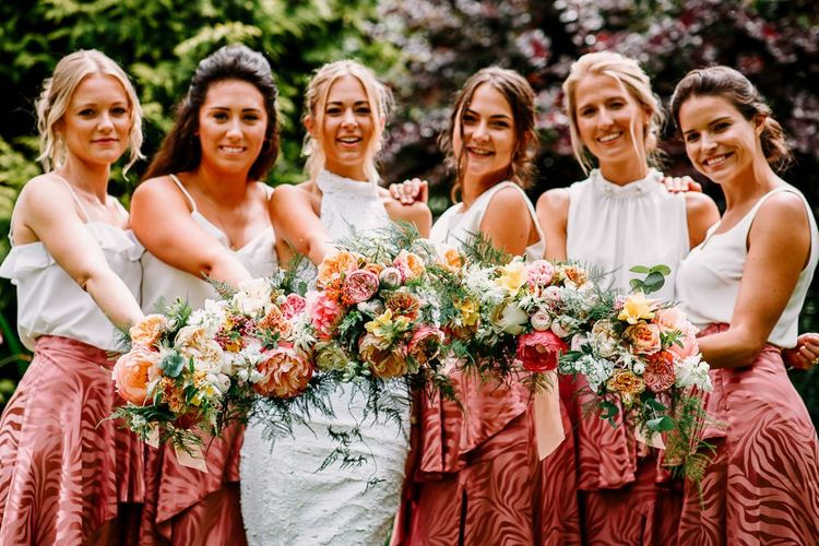 Backless wedding dress with bridesmaids in pink skirt and beautiful bouquets