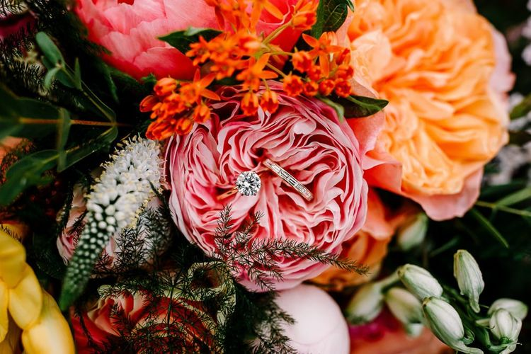 Bright wedding flowers with David Austin roses and wedding rings