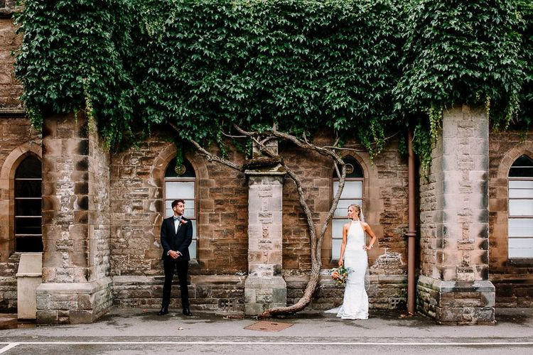 Bride and groom pose outside wedding venue