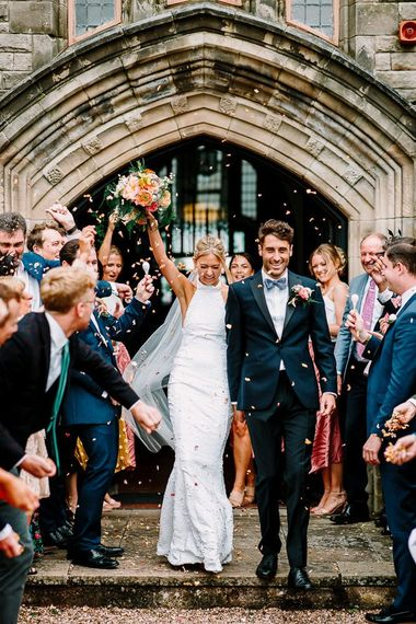 Confetti exit for bride in backless wedding dress and groom in bowtie