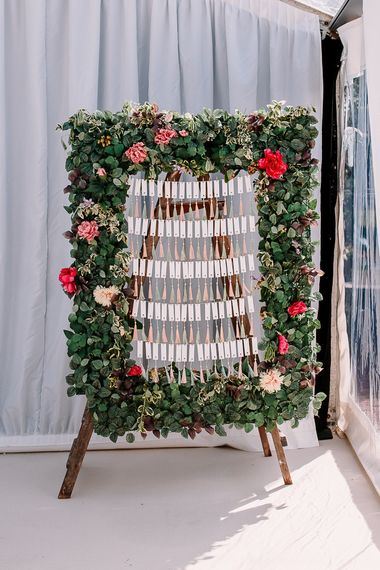 Stunning wedding seating plan with flowers and tassels