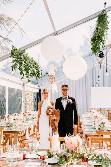 Bride and groom with wedding balloon and pet dog
