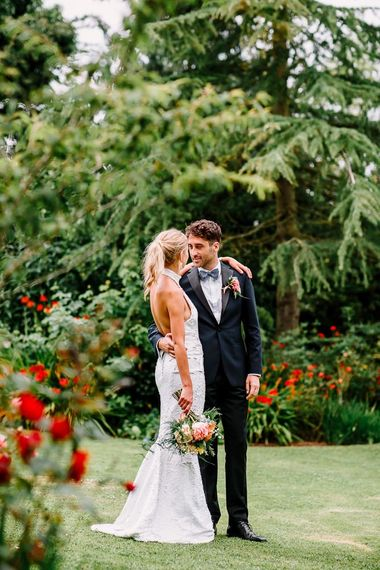 Backless wedding dress with groom in bowtie