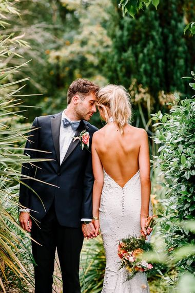 Backless wedding dress with ponytail and groom in bowtie