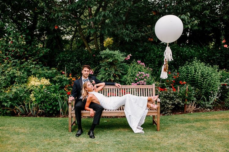 Bride and groom pose with wedding balloons
