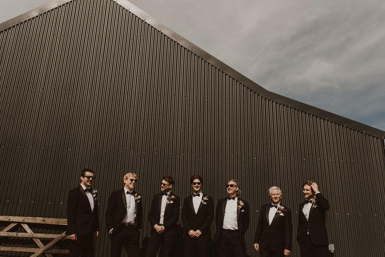 Groom with groomsmen in classic black tuxedo wedding suit