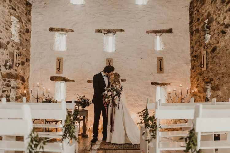 Bride and groom kiss during Wales wedding ceremony