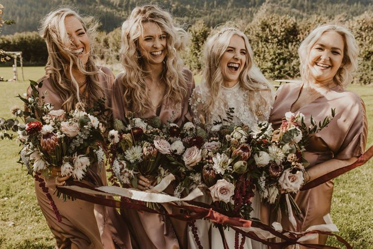 Bridesmaids in blush dresses with floral bouquets