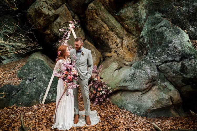 Bride in High Street Wedding Dress and Groom in Check Suit Standing in Front of an Altar Decorated with Pink Wedding Flowers