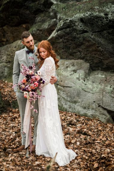 Bride in Lace ASOS Wedding Dress and Groom in Light Grey Suit Embracing