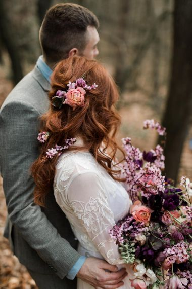 Bride and Groom Embracing Showing off Brides Beautiful Wedding Hair with Fresh Flowers