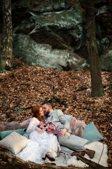 Bride and Groom Laying Down in Cushion Filled Chill out Area
