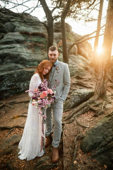 Golden Hour Portrait with Bride in Boho Wedding Dress and Groom in Grey Suit Cuddling