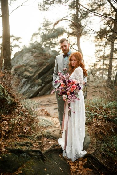 Groom in Grey Suit, Blue Shirt & Purple Bow Tie Embracing Bride with Boho Wedding Dress and Oversized Pink Wedding Bouquet