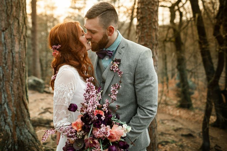 Bride Holding Pink Blossom and Purple Tulip Spring Bouquet whilst Kissing Her Groom at Sunset