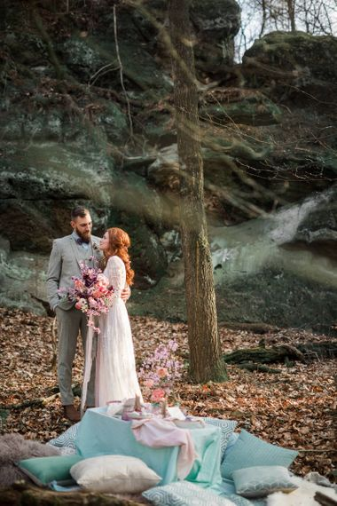 Boho Bride in Lace Wedding Dress with Groom in Contemporary Grey Suit Standing Next to Their Sweetheart Table