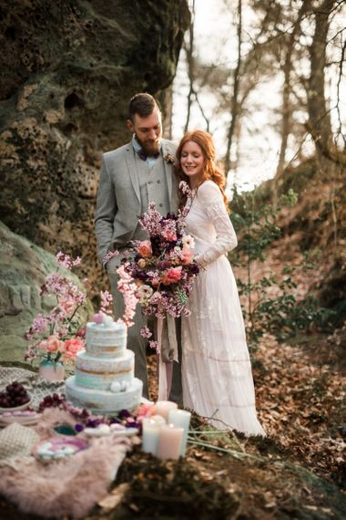 Boho Bride and Groom Standing by Their Wedding Cake