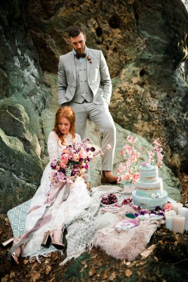 Boho Bride in Lace Wedding Dress with Groom in Grey Suit Sitting By Their Dessert Table Full of Treats and Decor