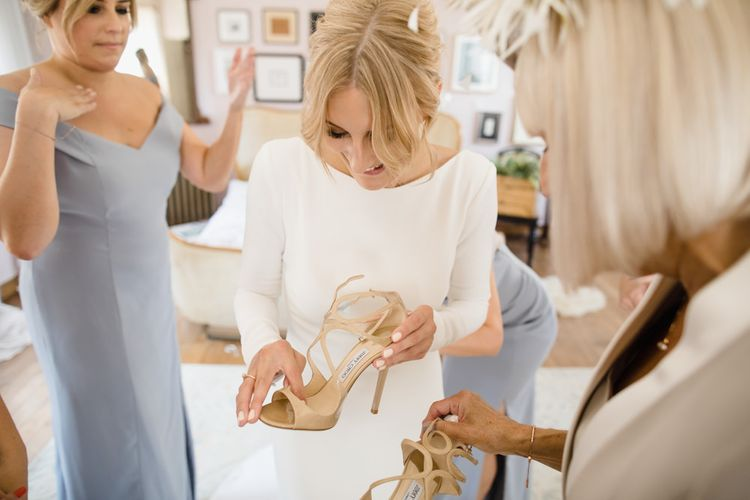 Bride in Long Sleeved Wedding Dress with Plunging V-Back and Cuff Buttons by Pronovias | Bridal Up Do | Lance by Jimmy Choo Nude Strappy Shoes | Bridesmaids in Grey Off-Shoulder Dessy Dresses with Side Split | Ivania Pronovias Wedding Dress with Long Sleeves and Minimalist Styling | Chris Barber Photography