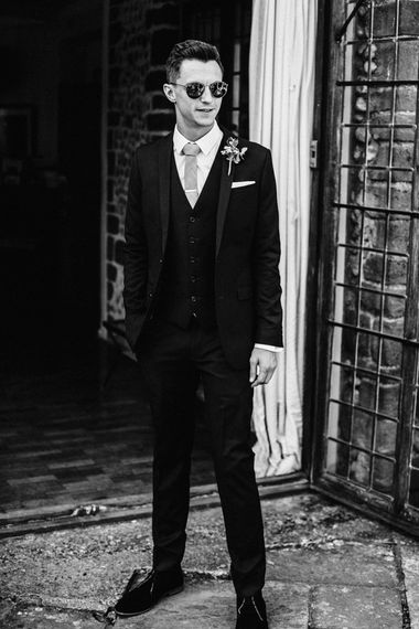 Groom in Black Three-Piece Suit with Grey Tie and Personalised Tie Clip | Ivania Pronovias Wedding Dress with Long Sleeves and Minimalist Styling | Chris Barber Photography