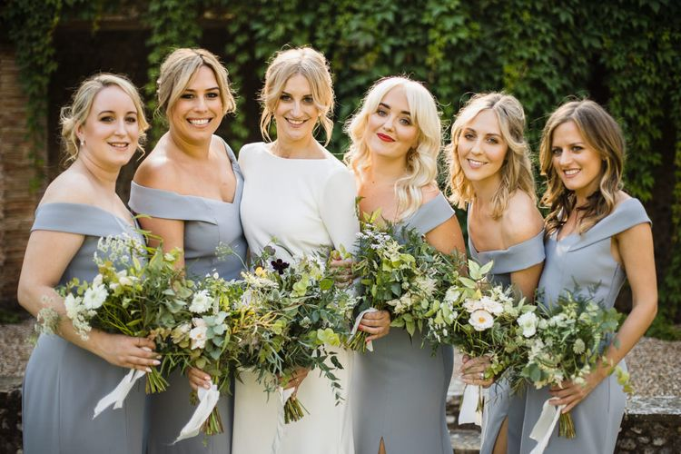 Bride in Long Sleeved Wedding Dress with Plunging V-Back and Cuff Buttons by Pronovias | Bridal Up Do | Bridesmaids in Grey Off-Shoulder Dessy Dresses with Side Split | Bouquets of Scabious, Ammi Majus, Veronica, Snowberries, Chocolate Cosmos, Black Scabious, Cafe au Lait Dahlias and Majolica Spray Roses with White Trailing Ribbon | Ivania Pronovias Wedding Dress with Long Sleeves and Minimalist Styling | Chris Barber Photography