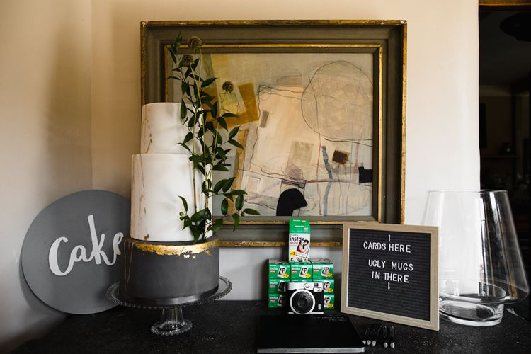 Three Tier Wedding Cake with White and Grey Icing, Gold Leaf Detail and Grey Ribbon | Polaroid Photobooth | Ivania Pronovias Wedding Dress with Long Sleeves and Minimalist Styling | Chris Barber Photography
