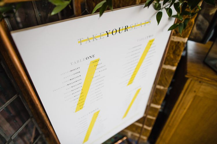 Seating Plan with Neon Stripes Displayed in Copper Stand with Foliage Garland | Ivania Pronovias Wedding Dress with Long Sleeves and Minimalist Styling | Chris Barber Photography